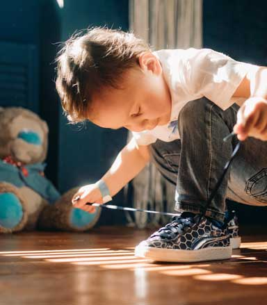 Young child learning to tie his shoes